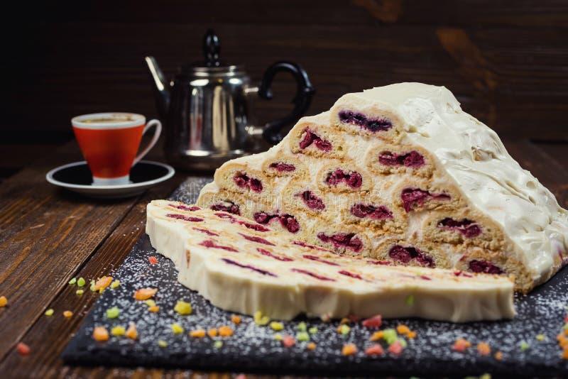 Baka ihop med kräm och körsbär och koppen kaffe, smaklig kaka med w royaltyfria foton