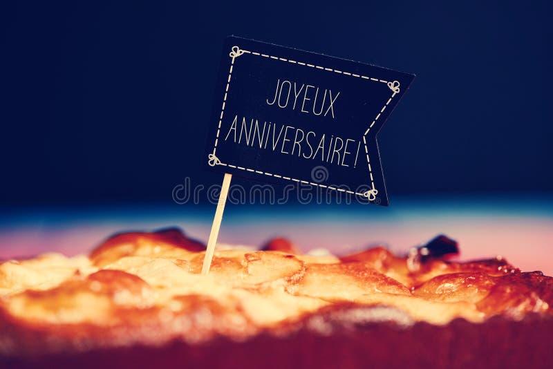 Baka ihop med textjoyeuxanniversaire, lycklig födelsedag i franskt royaltyfria foton