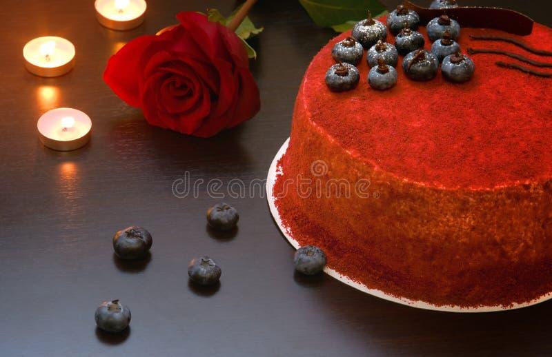 Baka ihop röd sammet på tabellen bredvid rosen som smyckas med blåbärbär och choklad royaltyfri fotografi