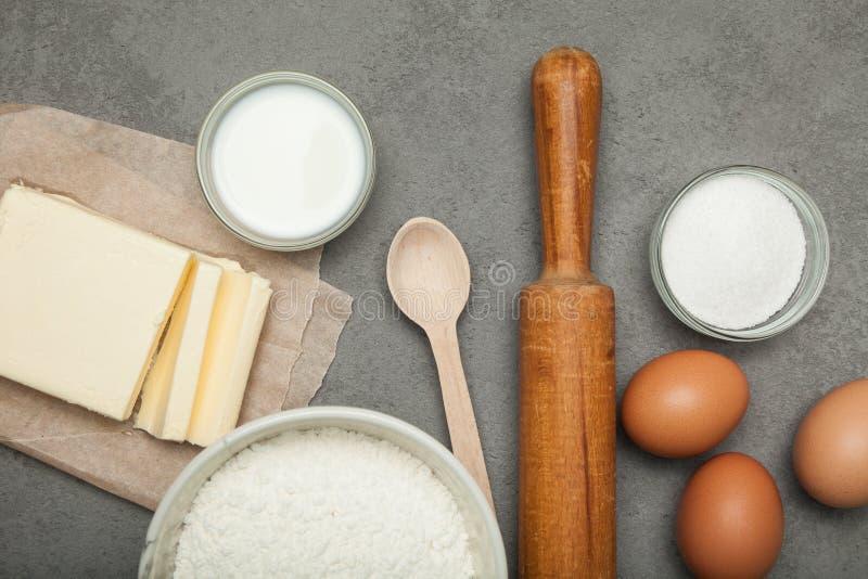 Baka ingredienser: ägg och mjöl på grå bakgrund, degförberedelse royaltyfri foto