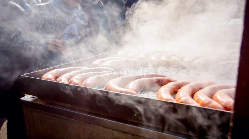 Baka läckra saftiga korvar på den stora grillfestplattan, rökig sikt royaltyfria foton