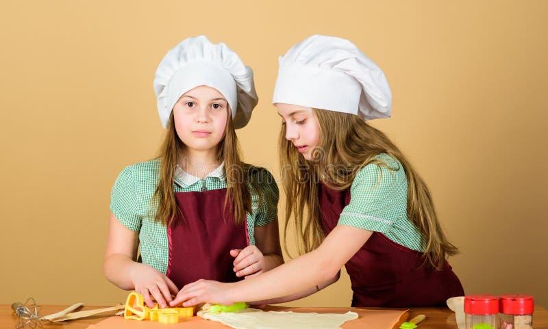Baka ljust rödbrun kakor Flickasystrar som har rolig ljust rödbrun deg Ungar som tillsammans bakar kakor Ungeförkläden och ko royaltyfri foto