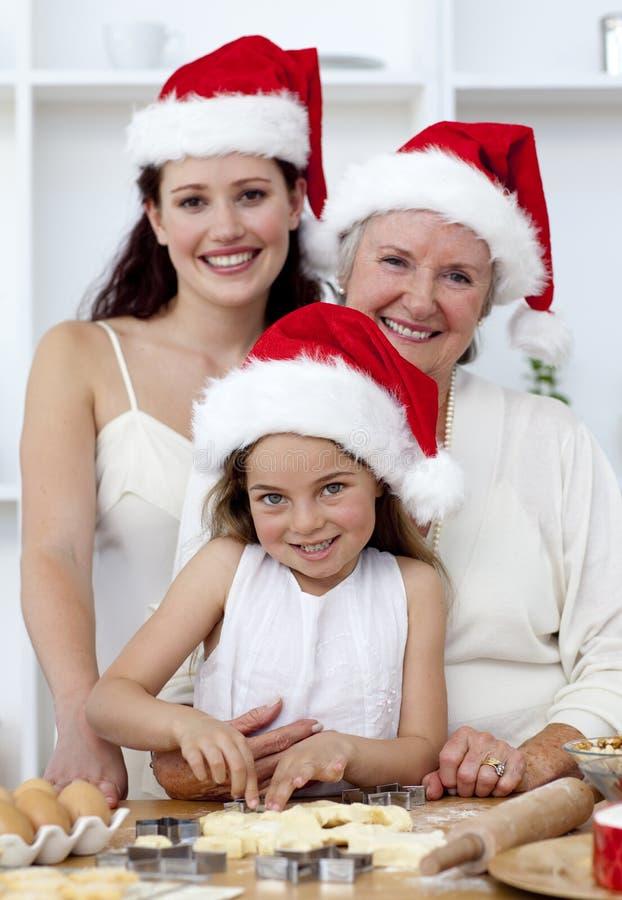 baka lycklig cakesjulfamilj arkivfoto
