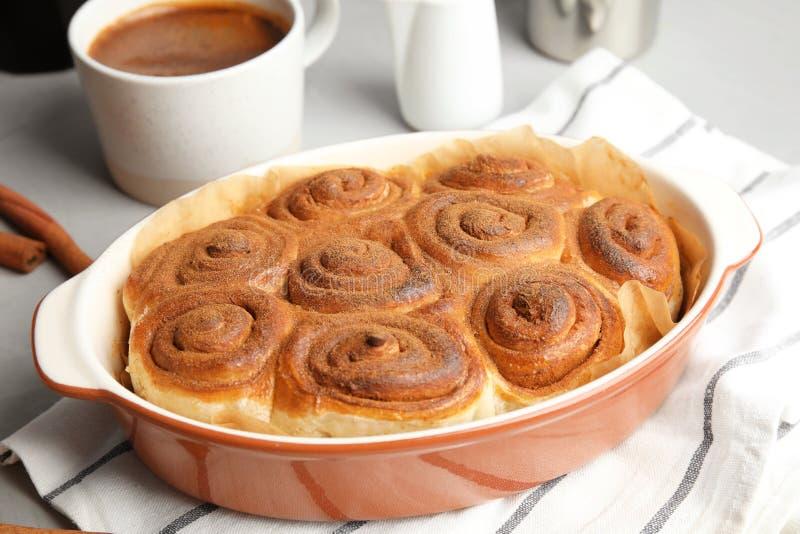 Baka maträtten med kanelbruna rullar royaltyfri fotografi