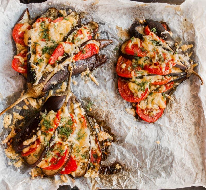 Bakad aubergine i en fanform på en bakplåt, bästa sikt Lagat mat med tomater och ost arkivfoto