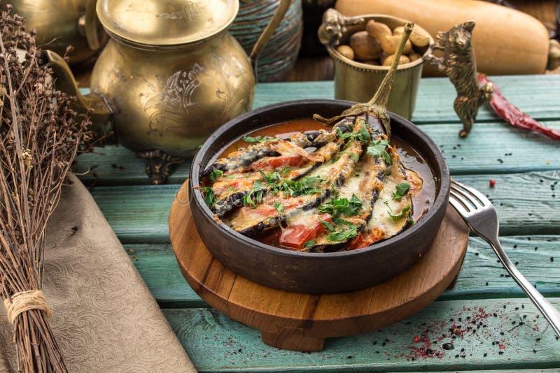 Bakad aubergine som stoppas med kött, tomater, paprika, löken och ost på den blåa trätabellen arkivbild