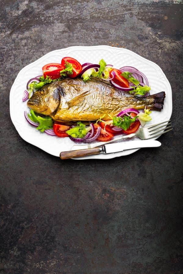 Bakad fisk Dorado Sallad för bakad och ny grönsak för Dorado fiskugn på plattan Havsbraxen eller grillad doradafisk och grönsaksa royaltyfria foton