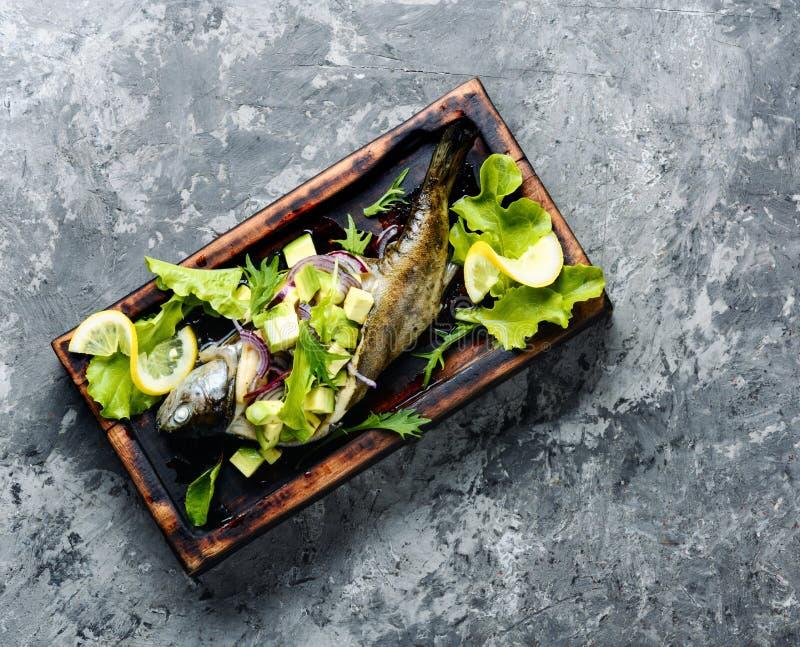 Bakad fisk med avokadot royaltyfria foton