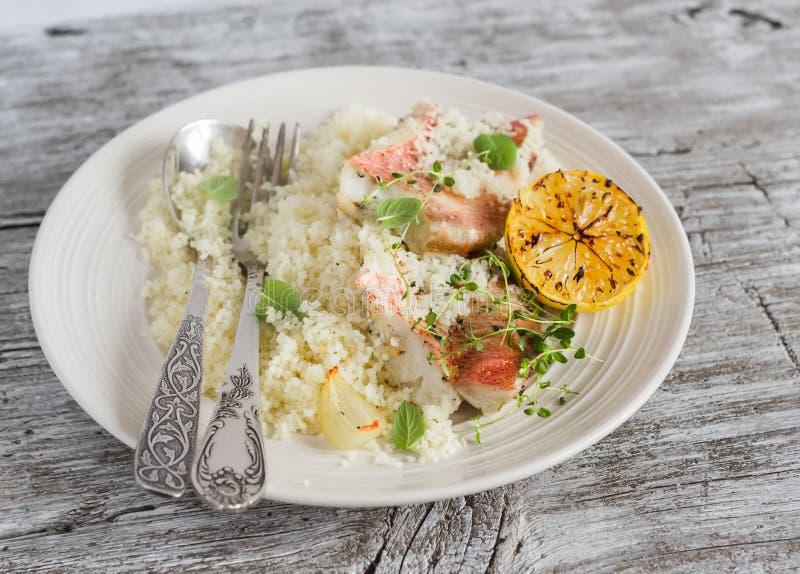 Bakad fisk med citronen och örter och cous cous på en vit platta, på ljus träyttersida arkivbilder