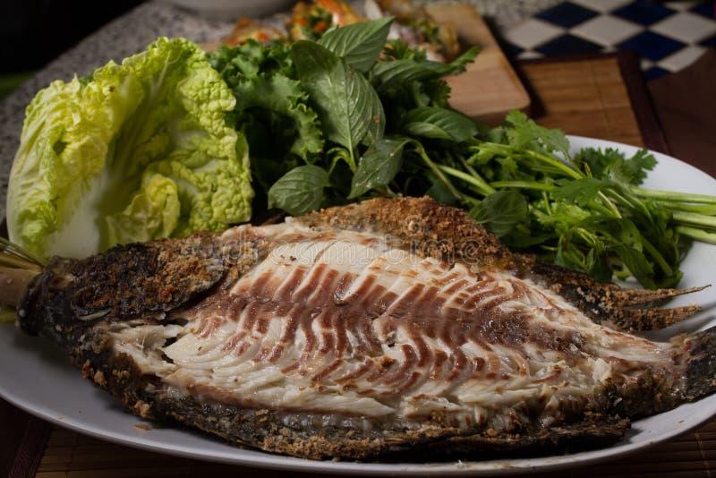 Bakad fisk med havs- sås royaltyfri bild