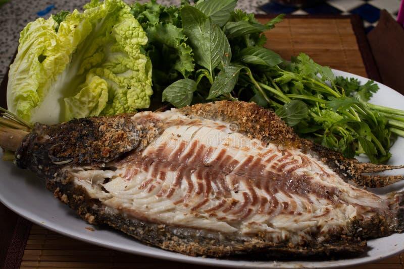 Bakad fisk med havs- sås royaltyfria bilder