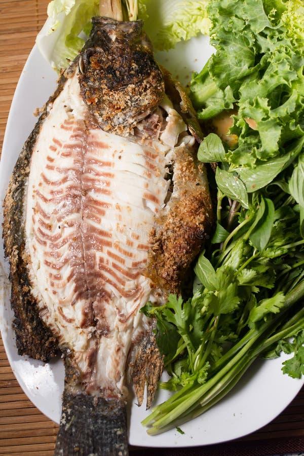 Bakad fisk med havs- sås arkivbild