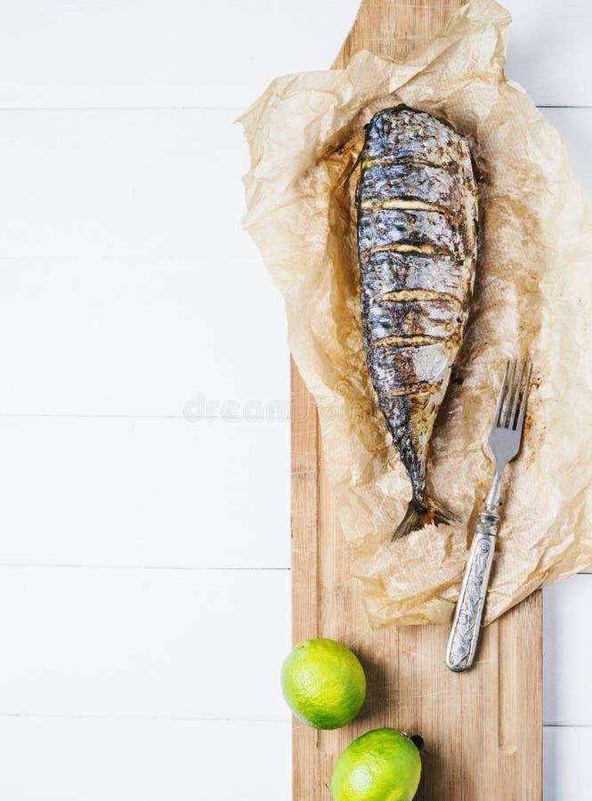 Bakad fisk med limefrukt på pergamentpapper och skärbrädan på en vit bakgrund av den gamla lodlinjen för bästa sikt för träbrädet arkivbild