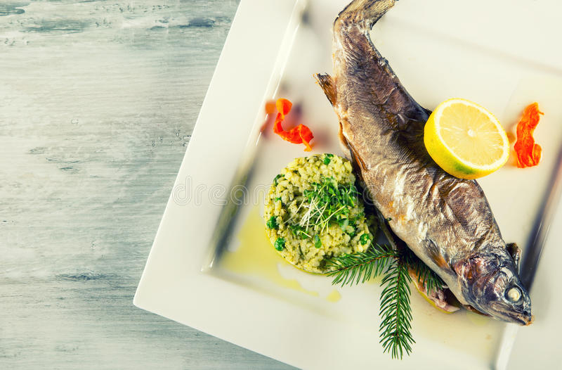 Bakad fisk på en platta med citronen och korngrynsgröt i en restaurang fotografering för bildbyråer
