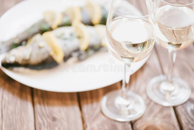 Bakad fiskmaträtt och två exponeringsglas av vitt vin arkivbilder