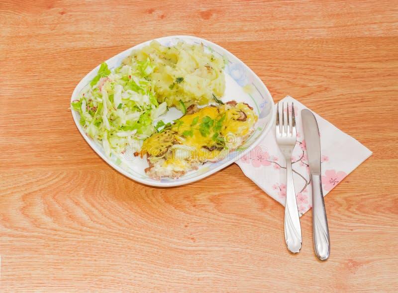 Bakad fläskkotlett med garnering av mosad potatisar och sallad royaltyfri bild