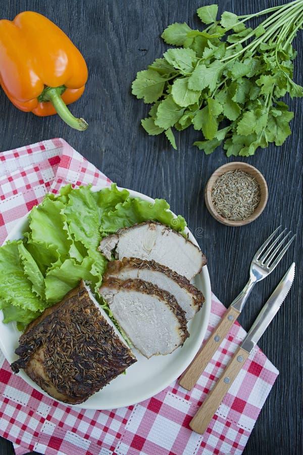 Bakad grisköttfläskkarré i kryddor som skivas på en vit platta med grön sallad m?rkt tr? f?r bakgrund arkivfoton