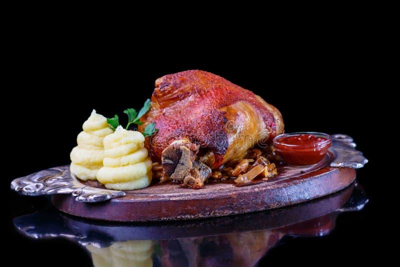 Bakad grisköttknoge med den mosade potatisar och surkålen royaltyfria foton
