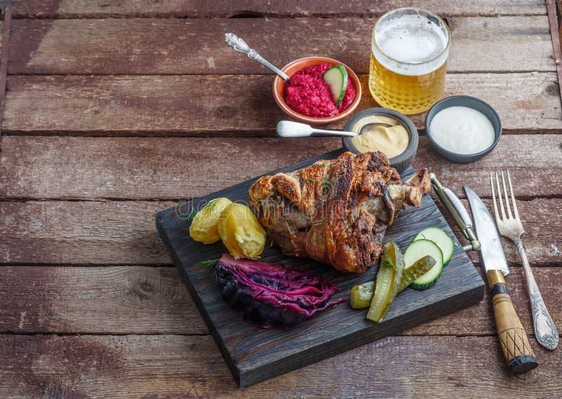 Bakad grisköttlägg med potatisen, kål och öl, kopieringsutrymme royaltyfri foto