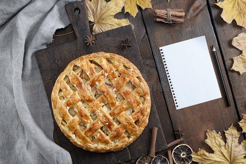 Bakad hel rund äppelpaj på ett brunt träbräde, smördeg arkivbild