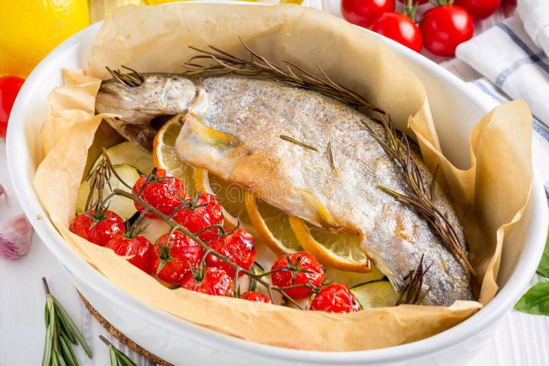 Bakad hel vit forellfisk i keramisk bakningmaträtt med zucchin royaltyfri fotografi