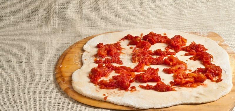 Bakad hemlagad pizza, organisk deg rullande och som täckas med krossade organiska tomater 7 royaltyfri foto
