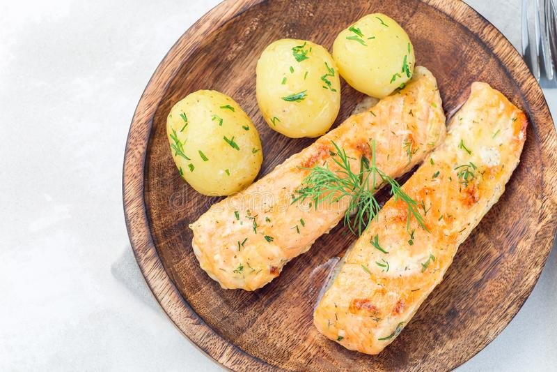 Bakad lax i krämig sås med den unga kokta potatisen som överträffas med smältt smör och huggen av dill på en träplatta som är hor royaltyfria bilder