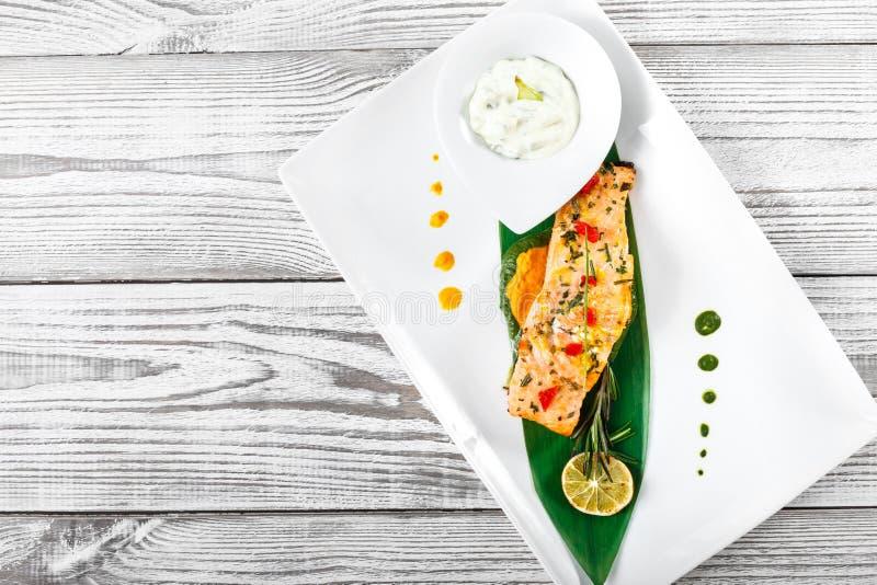 Bakad lax med den ostsås, rosmarin och citronen på träbakgrund varm maträttfisk royaltyfri fotografi