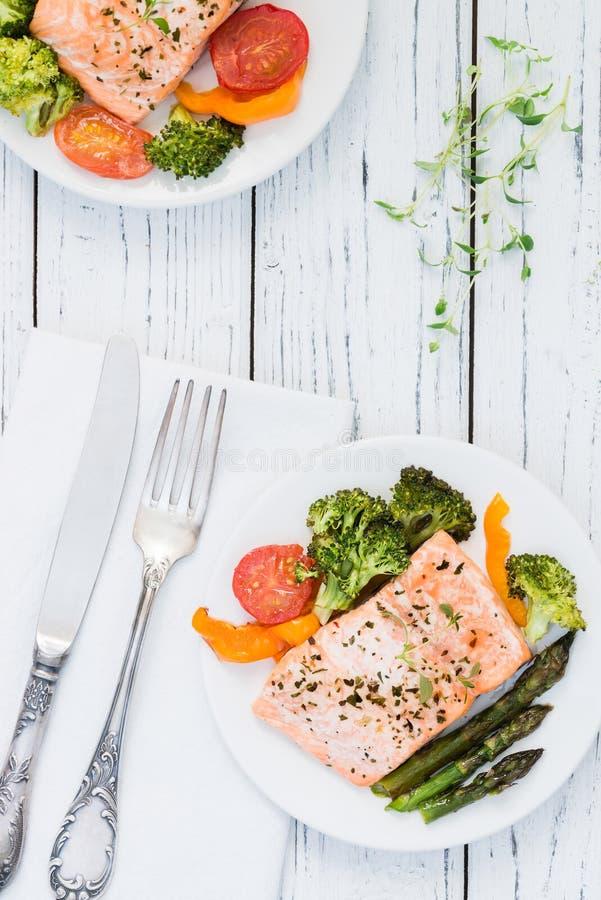 Bakad lax med grönsaker på plattan Trävit bordlägger royaltyfria foton
