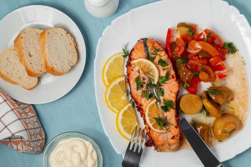 Bakad laxfilémedaljong med sallad av inlagda grönsaker och champinjoner på en vit platta på en blå bakgrund, bästa sikt, royaltyfri foto