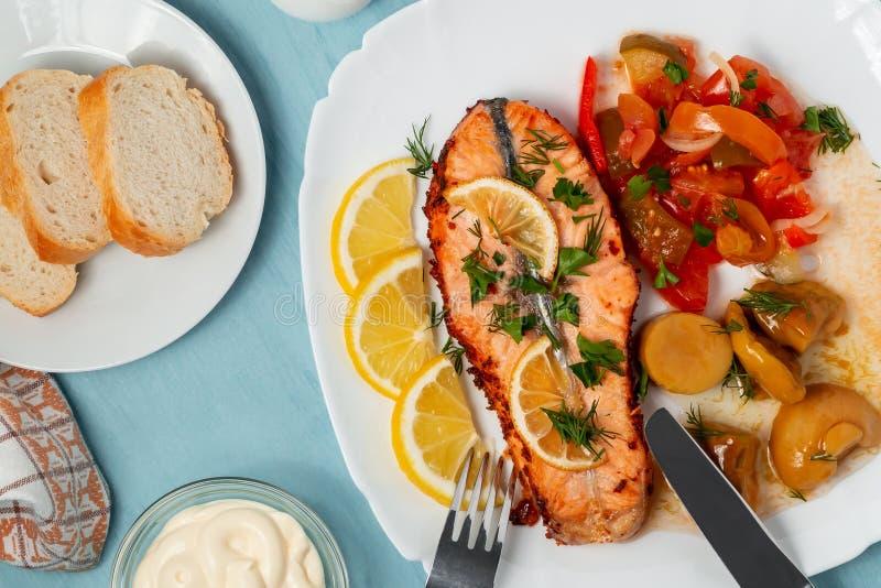 Bakad laxfilémedaljong med sallad av inlagda grönsaker och champinjoner på en vit platta på en blå bakgrund, bästa sikt, royaltyfri bild