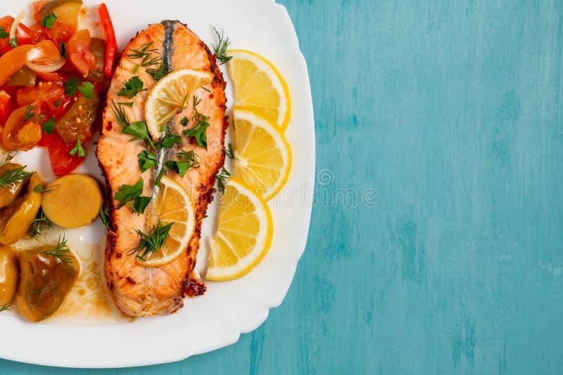 Bakad laxfilémedaljong med sallad av inlagda grönsaker och champinjoner på en vit platta på en blå bakgrund, bästa sikt, arkivfoton