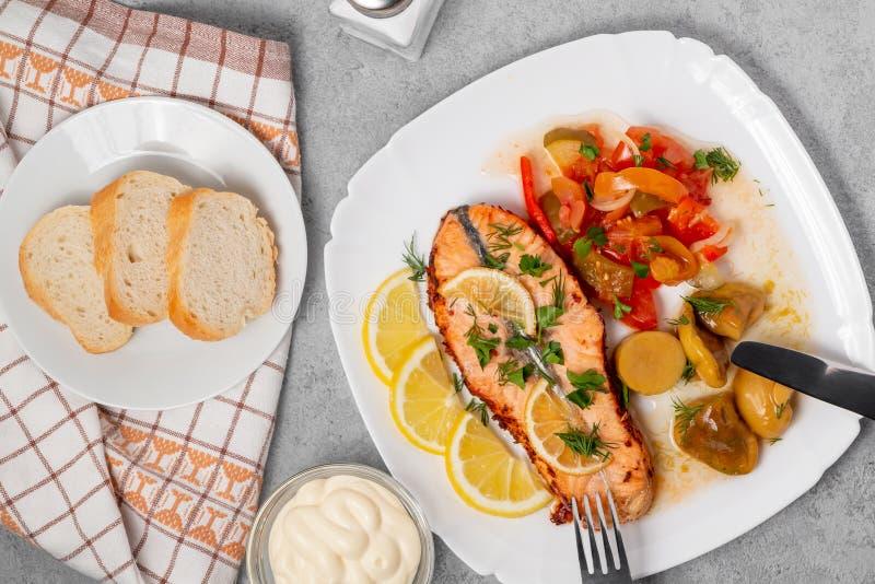Bakad laxfilémedaljong med sallad av inlagda grönsaker och champinjoner på en vit platta på en grå bakgrund, bästa sikt, arkivbild