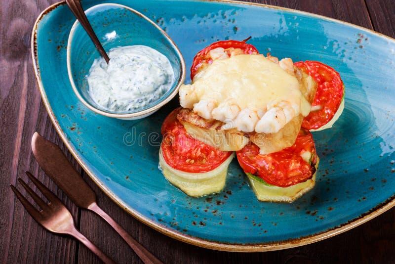 Bakad laxfisk med räka, ost, tomater, aubergine och sås på träbakgrund varm aptitretare fotografering för bildbyråer
