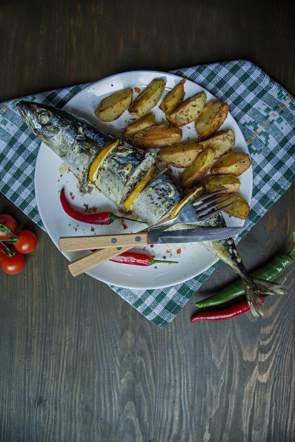 Bakad makrill med citronen och bakade potatisar p? en vit platta ?kerbruka produktgr?nsaker f?r ny marknad K?rsb?r chilipeppar be royaltyfria bilder