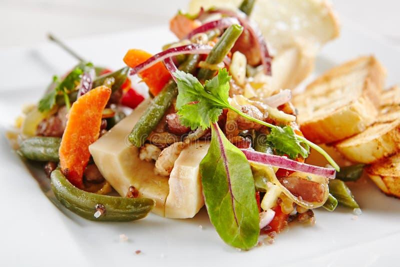 Bakad nötköttbenmärg med grönsaker på den vita plattan royaltyfria foton