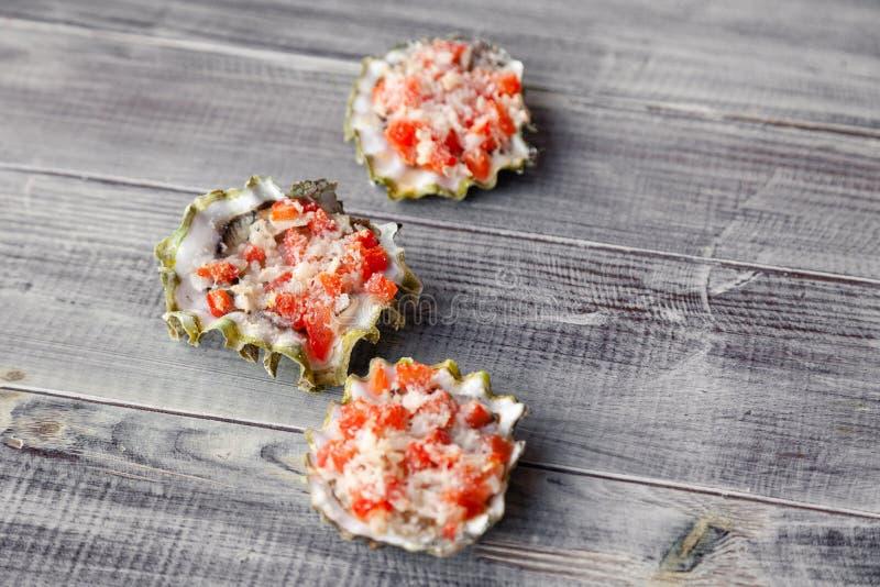 Bakad ostron som stoppas med tomaten, parmesan och kryddor, varm aptitretare i en havs- restaurang Begrepp av sjösidagallerstånge royaltyfria foton