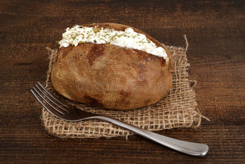 Bakad potatis med gräddfil- och jordningsgräslökar royaltyfri fotografi