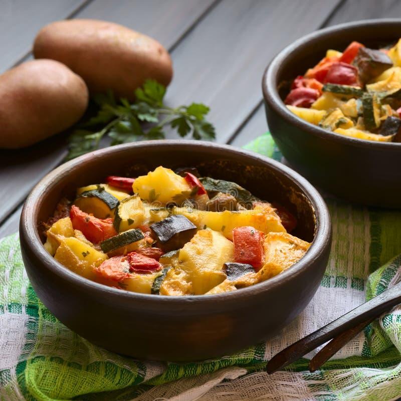 Bakad potatis-, zucchini-, aubergine- och tomateldfast form arkivfoton