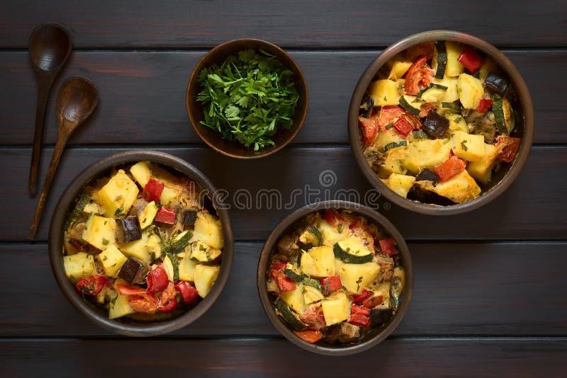 Bakad potatis-, zucchini-, aubergine- och tomateldfast form fotografering för bildbyråer