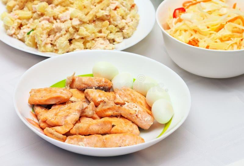 Bakad röd fisk, vaktelägg, grönsaksallad arkivbilder