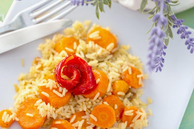 Bakad r?d peppar och lagade mat vita ris med l?ckra mor?tter p? en vit keramisk platta och bestickgaffel och kniv royaltyfri fotografi