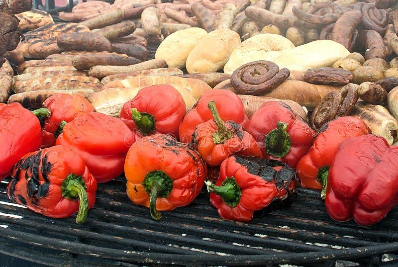 Bakad söt peppar, bröd, korv och grillat kött på gallret royaltyfri fotografi