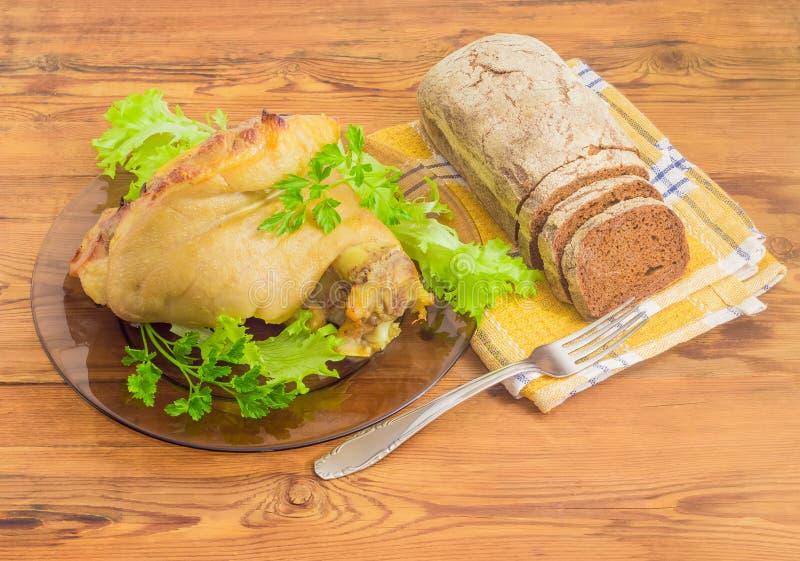 Bakad skinkahock på den glass maträtten och brunt bröd beside royaltyfri fotografi