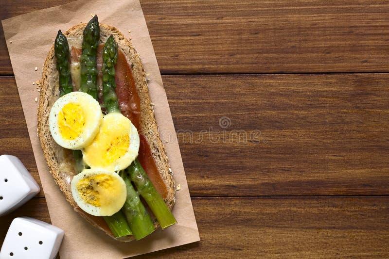 Bakad sparris, skinka, ägg och ostsmörgås fotografering för bildbyråer
