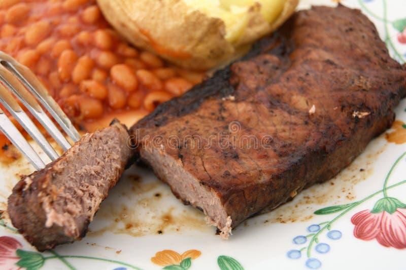 bakad steak för ländstycke för grillfestbönapotatis arkivbild