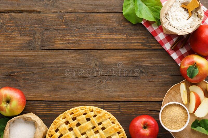 Bakade äppelpaj och ingredienser på trätabellen Säsongsbetonad bakelse arkivfoton