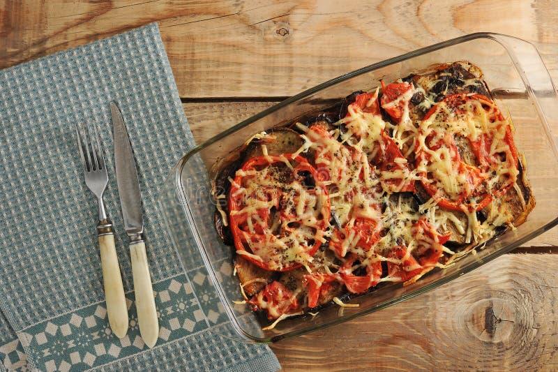 Bakade aubergine och tomater med ost och kryddor i den glass maträtten fotografering för bildbyråer
