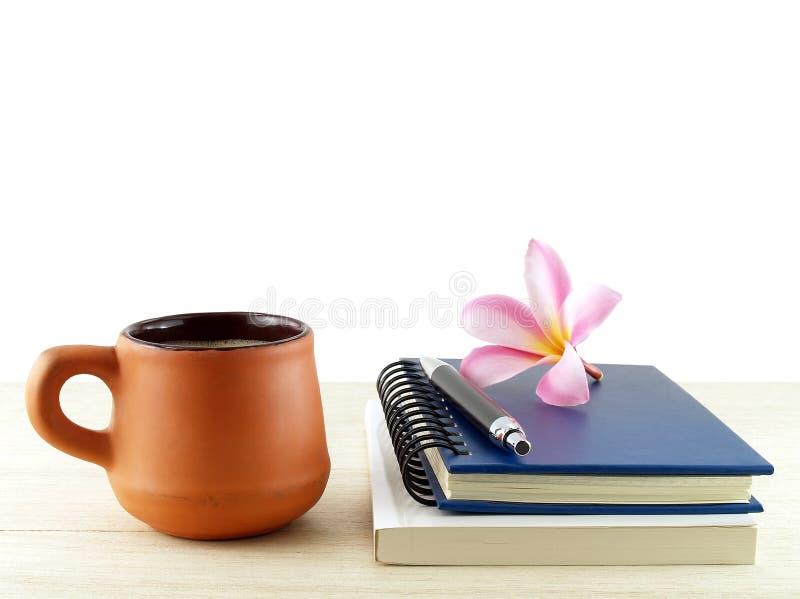 Bakade den bruna apelsinen för närbilden lerakaffekoppen, och två dagbokböcker med pennan och rosa färgplumeriafrangipanien blomm royaltyfria bilder