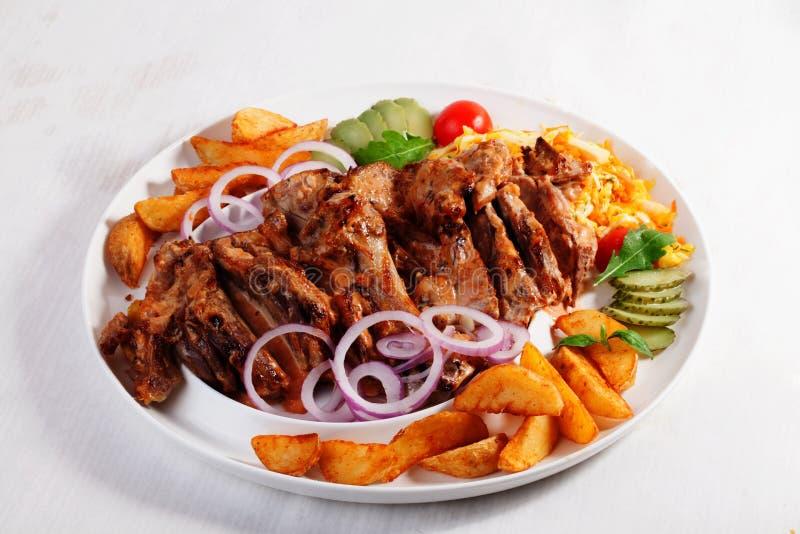 Bakade enorma potatisskivor för kött, inlagd gurka, röd lök, tomater, körsbär, stor portion, maträtt, vit, bakgrund, arkivbilder